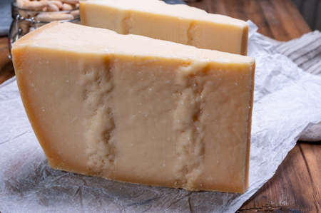 Big wedges of parmigiano-reggiano parmesan hard Italian cheese made from cow milk or Grana Padano close up Stock Photo
