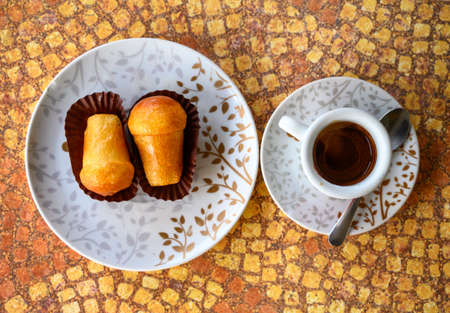 Classic italian espresso coffee served with homemade rum baba soft cake top view