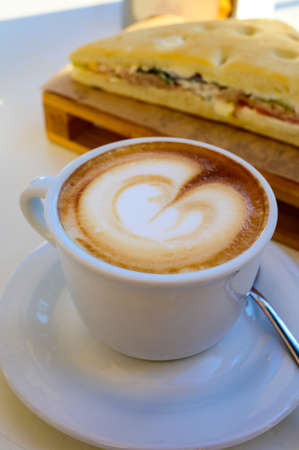 Breakfast coffee, Italian classic cappuccino with milk foam served in cafe close up