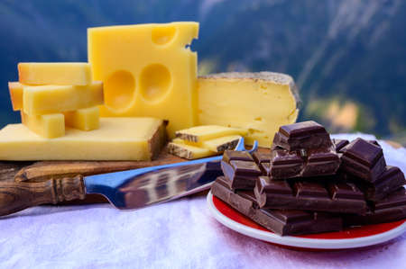 Tasty Swiss cheeses and dark pure chocolate, emmental, gruyere, appenzeller served outdoor with Alpine mountains peaks in summer on background 写真素材 - 155254161