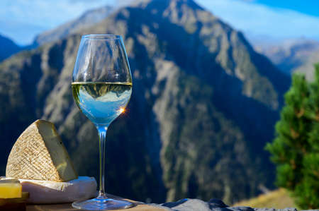 Tasty cheese and wine from Savoy region in France, beaufort, abondance, emmental, tomme and reblochon de savoie cheeses and glass of white wine served outdoor in summer with Alpine mountains peaks on background 写真素材 - 155254164