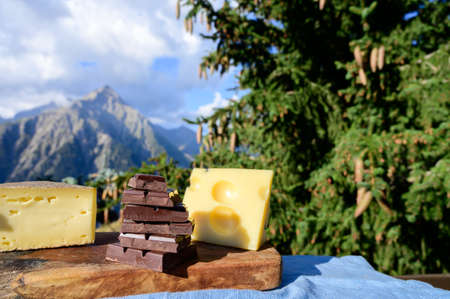 Tasty Swiss cheeses and dark pure chocolate, emmental, gruyere, appenzeller served outdoor with Alpine mountains peaks in summer on background
