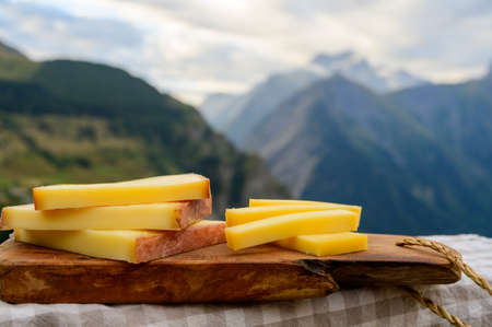 Cheese collection, French comte, beaufort or abondance cow milk cheese served outdoor with Alps mountains peaks in summer on background 写真素材 - 155254173