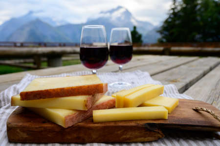 Cheese collection, French comte, beaufort or abondance cow milk cheese and glasses of red wine from Savoie served outdoor with Alps mountains peaks in summer on background
