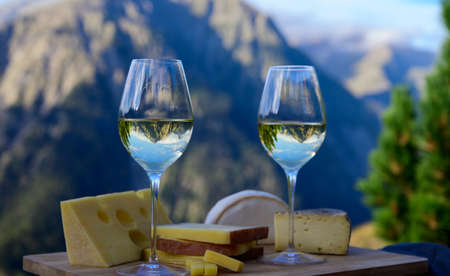 Tasty cheese and wine from Savoy region in France, beaufort, abondance, emmental, tomme and reblochon de savoie cheeses and glass of white wine served outdoor in summer with Alpine mountains peaks on background