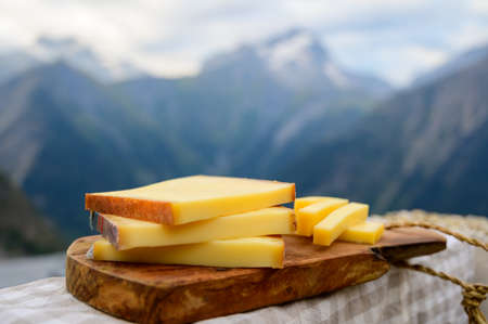 Cheese collection, French comte, beaufort or abondance cow milk cheese served outdoor with Alps mountains peaks in summer on background