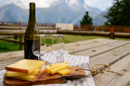 Cheese collection, French comte, beaufort or abondance cow milk cheese served outdoor with Alps mountains peaks in summer on background Archivio Fotografico