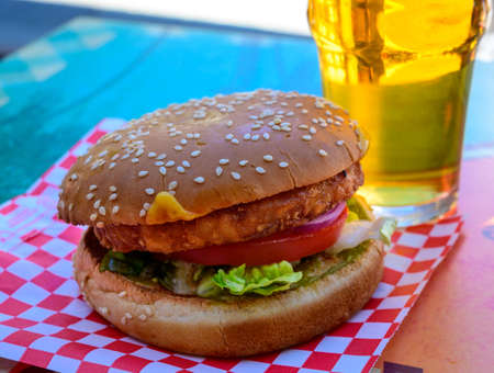 Fast food in bar served outdoor in sunny day, vegetarian hamburger and glass of cold beer close up