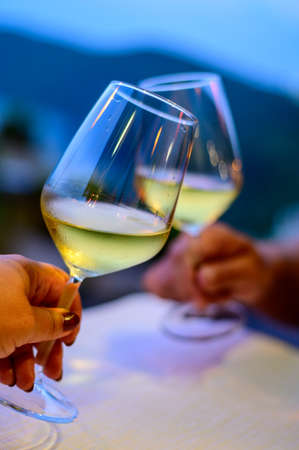 Hands with two clinking glasses of cold white wine in mountains cafe at night close up 写真素材 - 155373743