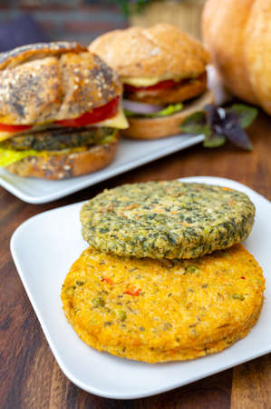 Making fresh and healthy vegetarian burgers with grilled spinach or pumpkin burgers, organic buns and vegetables close up