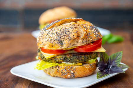 Eating of fresh and healthy vegetarian burgers with grilled spinach or pumpkin burgers, organic buns and vegetables close up 写真素材 - 155595771