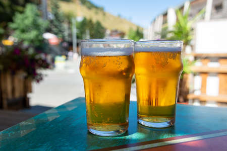 French cold beer in misted glasses served on outdoor terrace in small Alpine village in France close up