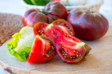 Making fresh green salad with big ripe raddish-purple heirloom tomatoes Black Crimea 写真素材