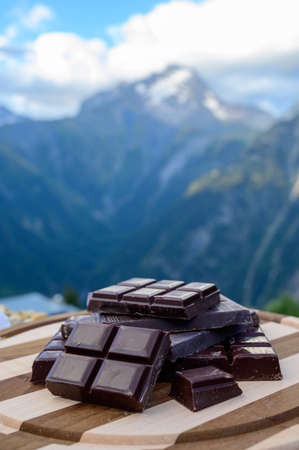 Handmade pure dark swiss chocolate and Alpine mountains on background in summer
