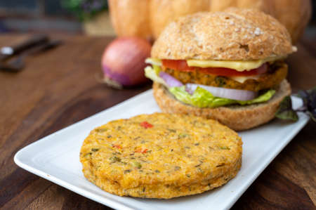 Making fresh and healthy vegetarian burgers with grilled pumpkin burgers, organic buns and vegetables close up