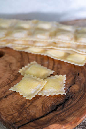 Handmade uncooked fresh ravioli with four cheeses filling, tasty vegetarian food close up