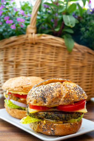 Eating of fresh and healthy vegetarian burgers with grilled spinach or pumpkin burgers, organic buns and vegetables close up 写真素材