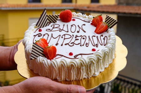 Traditional white Italian birthday cake with congratilations, buon compleanno means happy birthday close up 写真素材