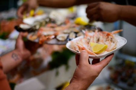 Catch of the day, waiter with fresh shrimps and sea food on ice in fish restaurant in Terracina, Italy close up 写真素材