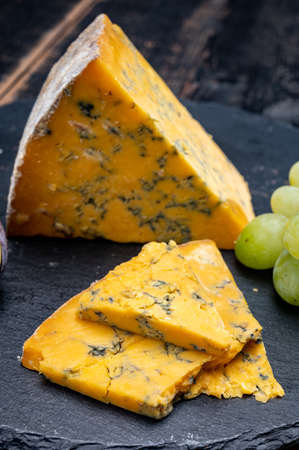 British matured yellow cheese blue shropshire, close up on black stone 写真素材