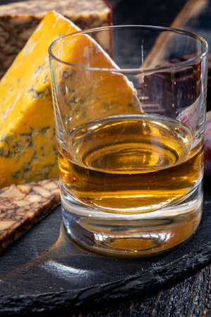 Tasting of Irish blended whiskey and cheeses from Ireland and UK, dark background
