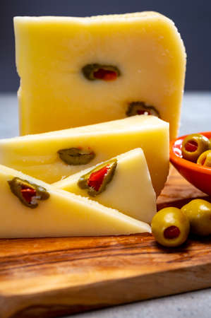 Cheese collection, fresh Italian pecorino cheese made from sheep milk filled with green olives stuffed with red sweet paprika 写真素材