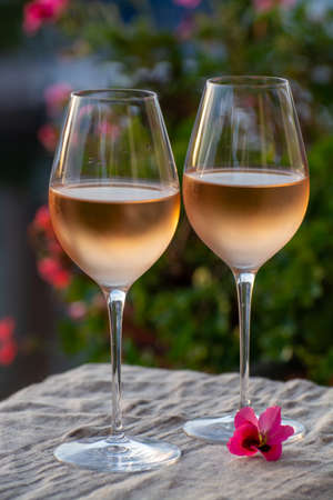 Tasting of local cold rose wine in summer on sunset with sail boats haven of Port grimaud on background, Provence, Var, France Banque d'images