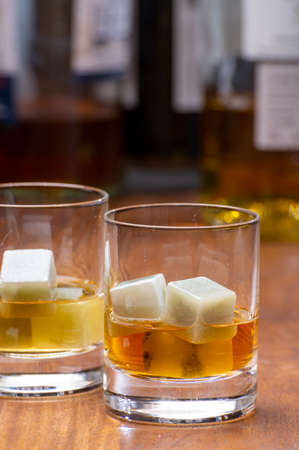 Tasting glass with strong alcoholic spirit drink whiskey, cognac, armagnac or calvados on wooden table