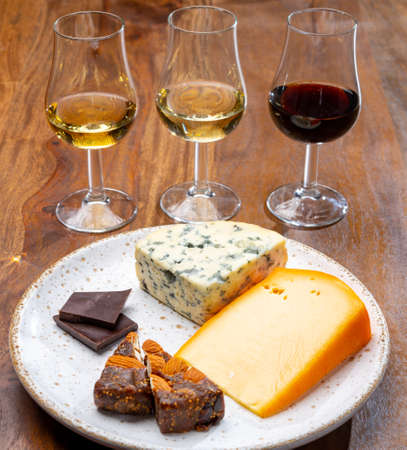 Tasting and pairing of different cheeses with strong alcoholic drinks, whiskey, cognac or calvados close up Reklamní fotografie
