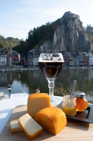 Glass of strong Belgian abbey beer and tasting of cheeses made with beer and fine herbs with view on Maas river in Dinant, Wallonia, Belgium