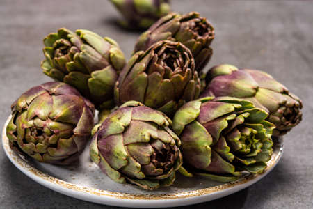 Fresh french petit violet artichokes heads cultivted in Brittany, France close up