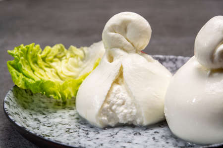 Cheese collection, italian soft white balls of burrata cheese made from mozzarella with cream inside in region Apulia close up 免版税图像
