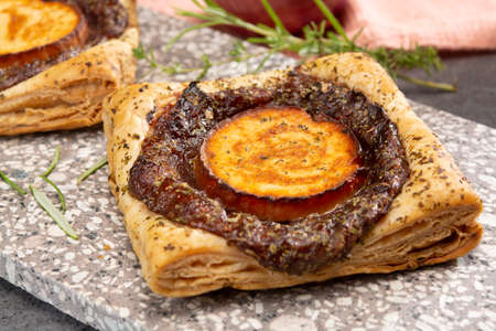 Fresh baked puff tarts with caramelized onion and goat cheese close up