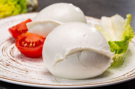 Ð¡heese collection, balls on soft white mozzarella bufala cheese served with green cos lettuce and tomato close up