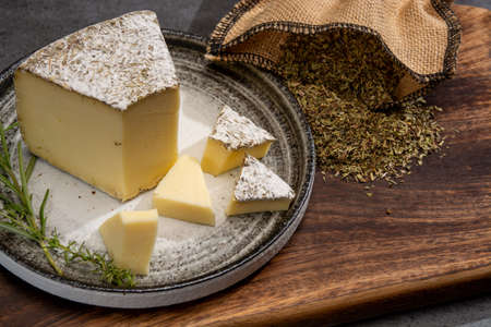 Cheese collection, French tomme cailladou cheese made with aromatic herbs of provence rosematy, thyme, origano close up