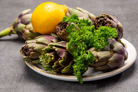 Fresh french petit violet artichokes heads cultivted in Brittany, France with lemon and parsley close up 写真素材