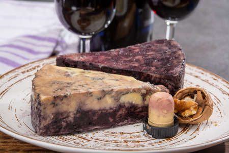 Cheese collection, blue stilton English cheese matured in red porto wine served as dessert with walnuts and glass ruby potro close up
