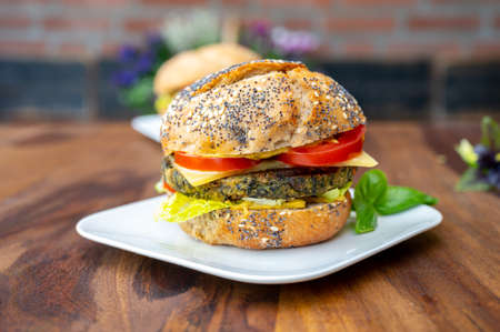 Eating of fresh and healthy vegetarian burgers with grilled spinach or pumpkin burgers, organic buns and vegetables close up Reklamní fotografie