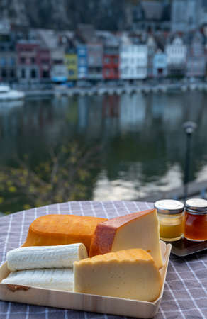 Cheese collection, tasty Belgian abbey cheeses made with brown beer and fine herbs and view on Maas river in Dinant, Wallonia, Belgium