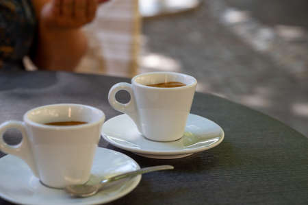 Drinking of strong black espresso coffee on outdoor terrace in cafe close up