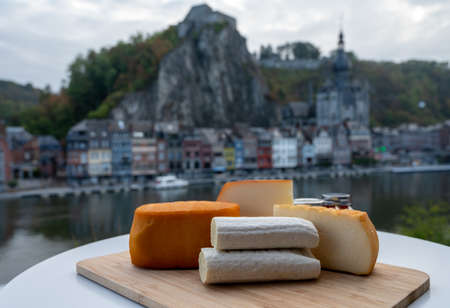 Cheese collection, tasty Belgian abbey cheeses made with brown beer and fine herbs and view on Maas river in Dinant, Wallonia, Belgium Stockfoto