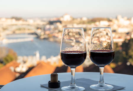 Tasting of different fortified dessert ruby, tawny port wines in glasses with view on Douro river, porto lodges of Vila Nova de Gaia and city of Porto, Portugal, on sunset