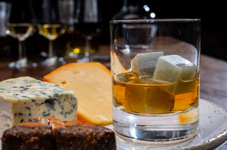 Tasting and pairing of different cheeses with strong alcoholic drinks, whiskey, cognac or calvados close up Фото со стока