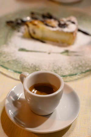 Classic italian espresso coffee served with homemade apple cheese cake with chocolate close up
