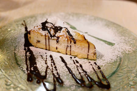 Piece of cheese cake with chocolate sauce and white sugar powder close up Stok Fotoğraf