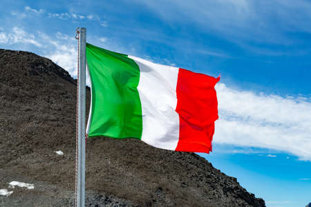 Green-white-red national italian flag waving on mast in sunny day