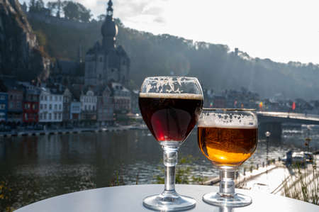 Drinking of dark and strong Belgian abbey beer with cheeses in sunny day with nice view on Maas river and town Dinant, Belgium Banque d'images