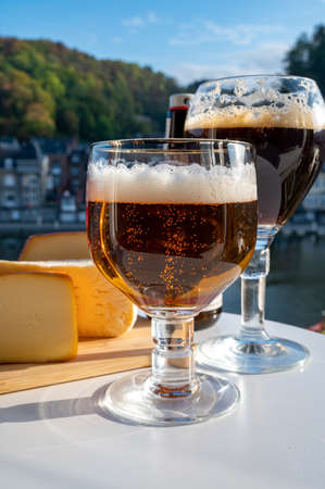 Drinking of dark and strong Belgian abbey beer with cheeses in sunny day with nice view on Maas river and town Dinant, Belgium