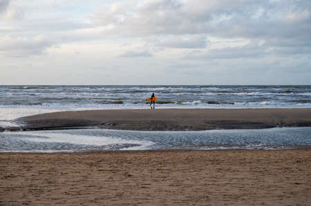 Surfer finished his training on cold water of North sea near Zandvoort in Netherlands in winter Stockfoto