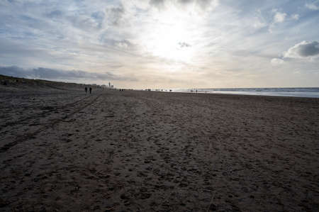 Unidentified people walking on wide sandy beach or North sea near Zandvoort in Netherlands Stockfoto